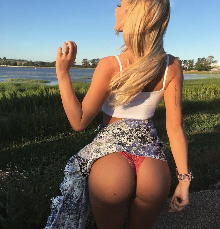 русская красавица игриво показывает свои ягодицы под юбкой