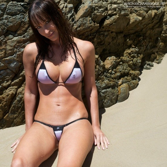 загорает сидя попой на морском песке