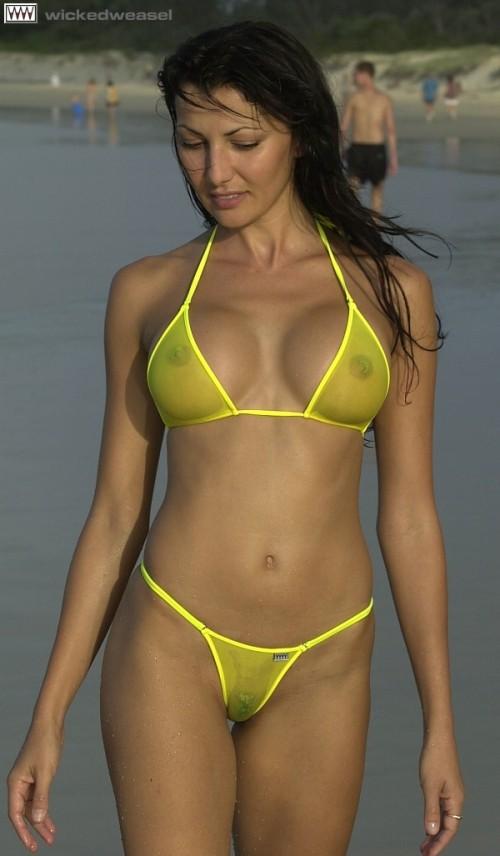 брюнетка в моде на пляже в прозрачном купальнике