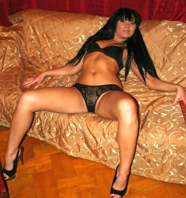 вульгарная поза с раздвинутыми ногами вульгарной женщины на диване дома