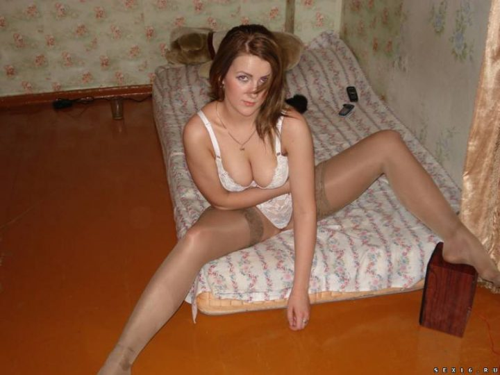позирует на полу сидя на матрасе