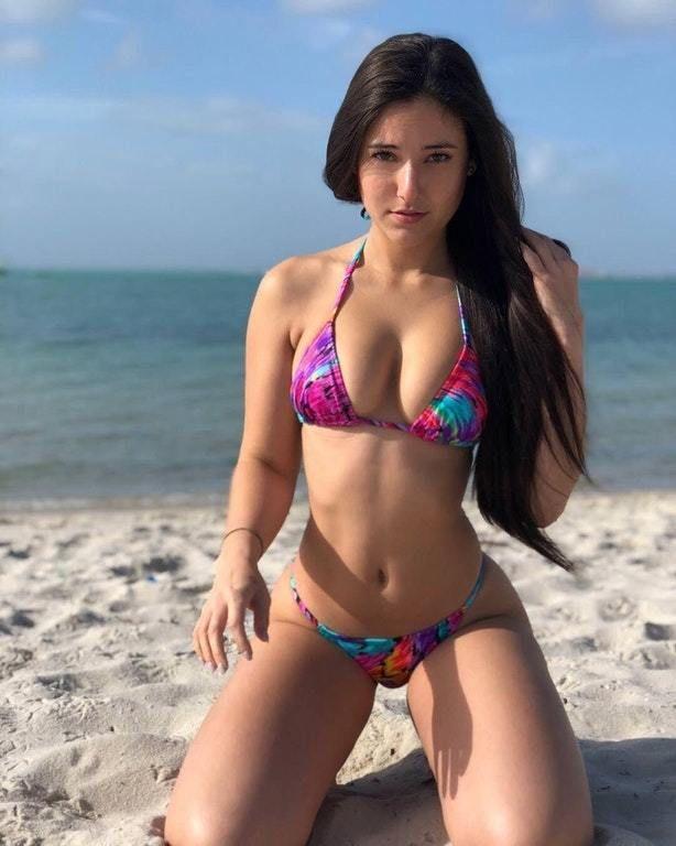 в ярком купальнике на песке у моря