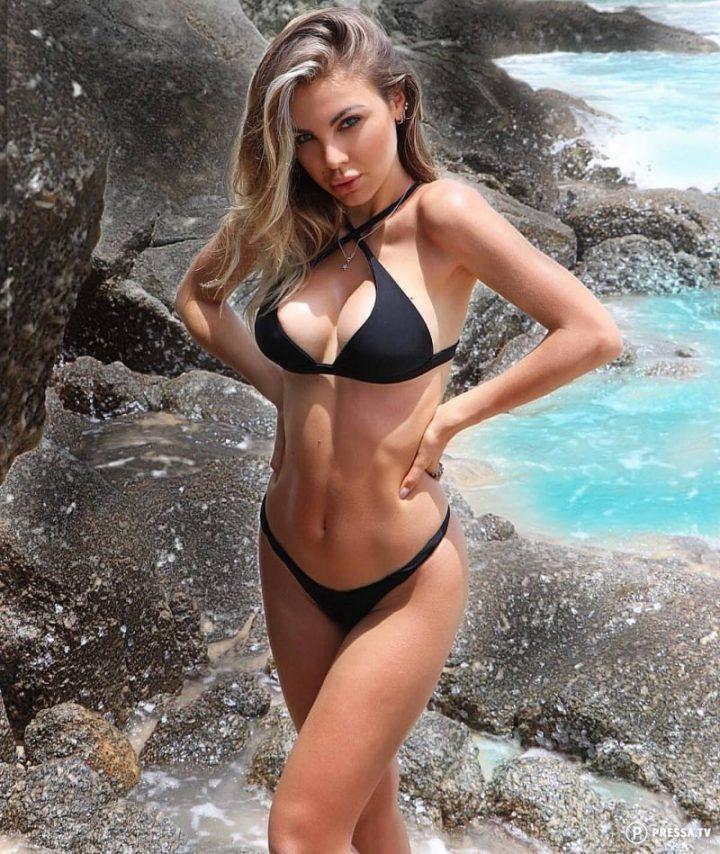 красивая девушка в черном купальнике среди камней
