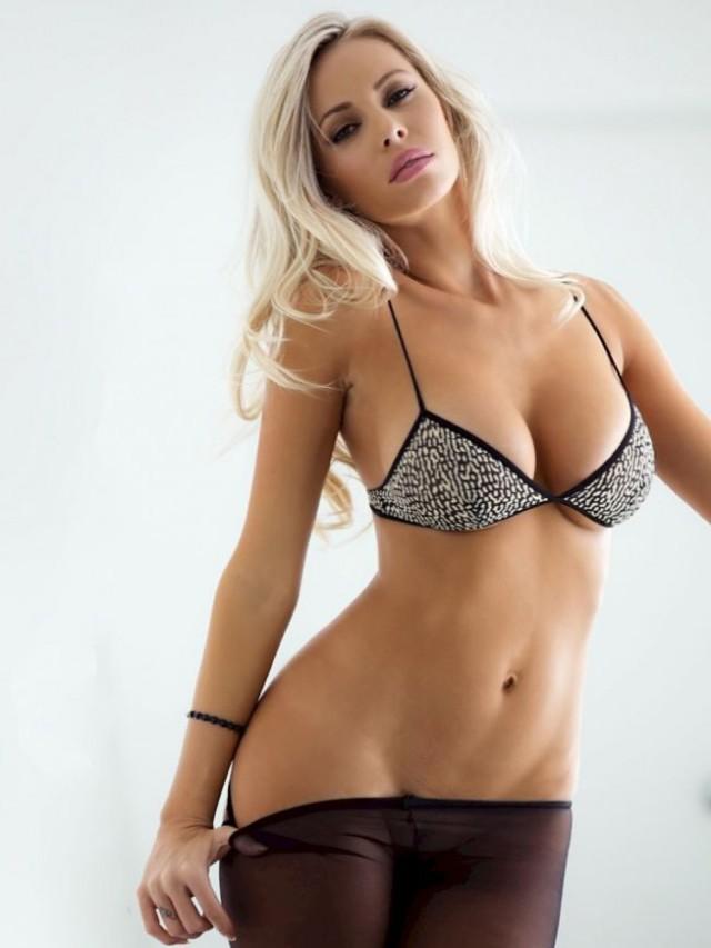 блондинка без трусиков медленно снимает с себя колготки