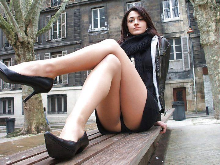 миленькая брюнетка с длинными ногами на скамейке возле дома