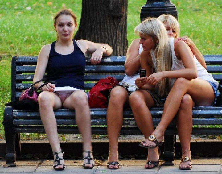 три телочки светят своими трусами, сидя на скамейке в парке