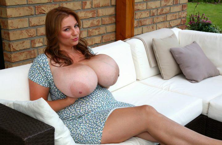милфа на летнем дворике, сидя на диване, оголила свою большую натуральную грудь