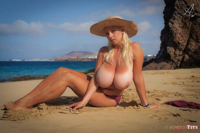 позирует на морском пляже топлесс, в стиле ню