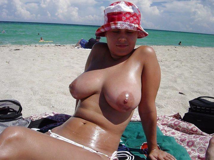 загорает топлесс на морском пляже