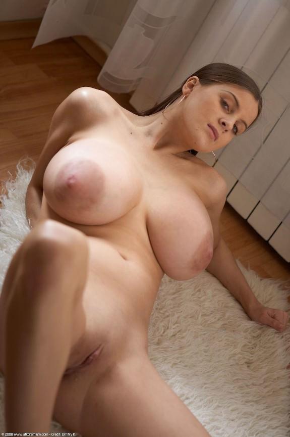 молодая девушка с милым личиком и очень большой грудью позирует голой на полу дома