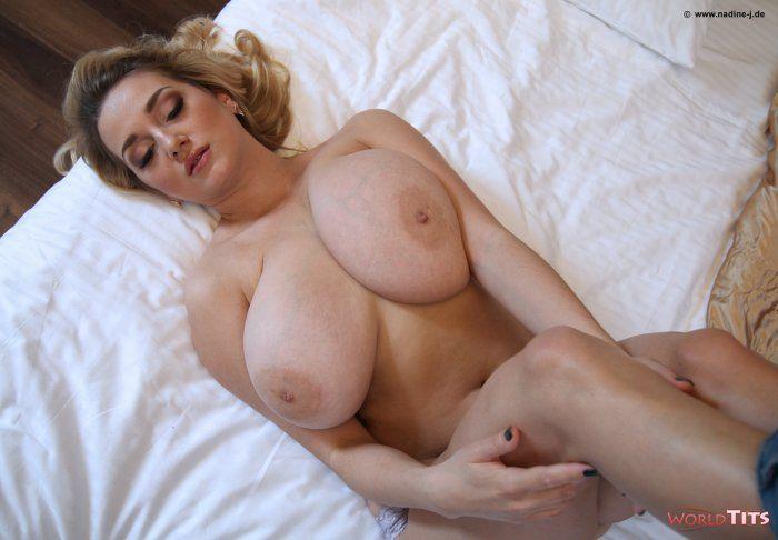 русоволосая красавица задрала вверх свои ноги, лежа на кровати