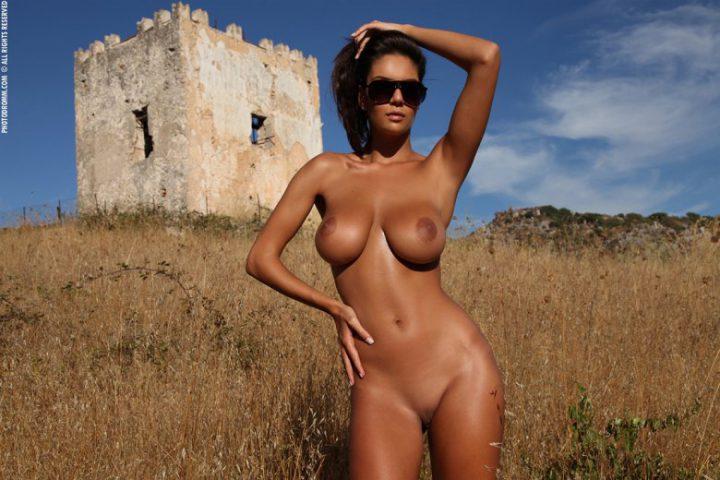 загорелая телочка в солнцезащитных очках позирует голой в поле