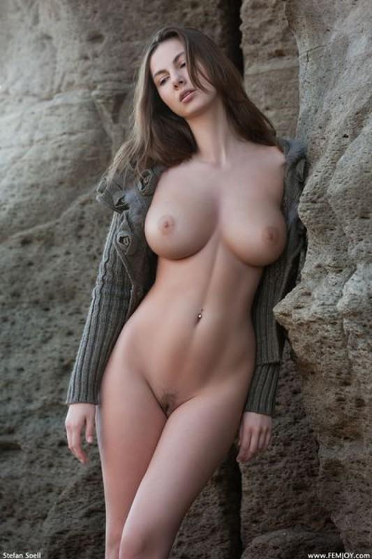 знойная русская красавица в мечтательной позе у камней