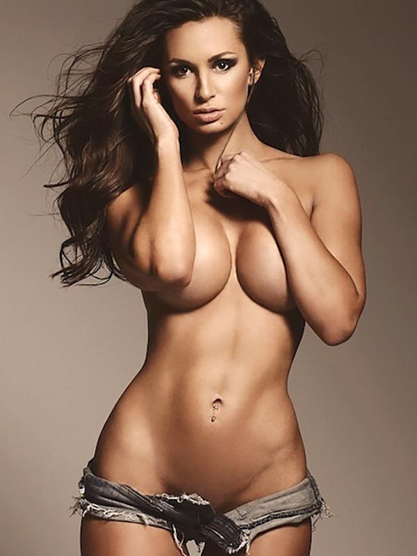 модель в очень коротких шортиках прикрывает груди руками