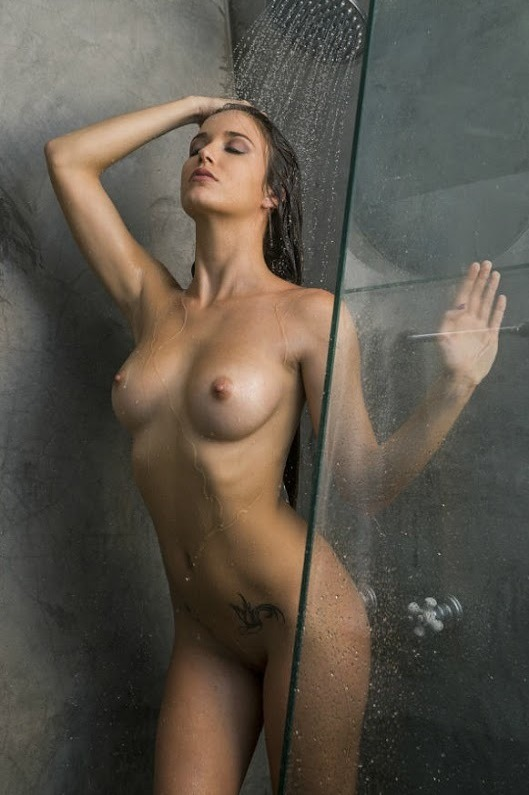 принимает душ в ванной комнате
