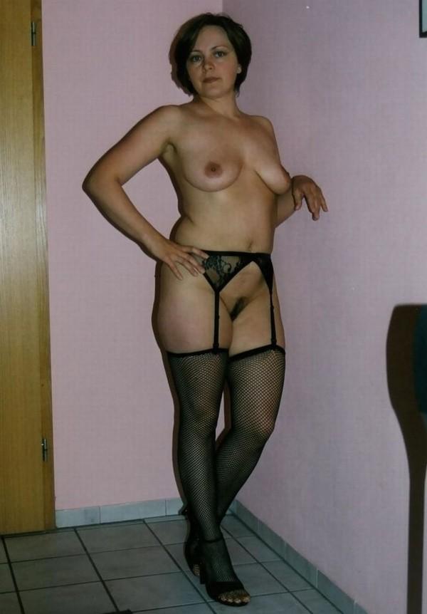 красивая женщина с хорошей фигурой в черных чулках и поясом с подвязками
