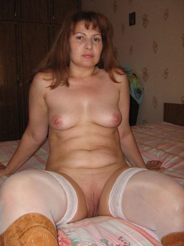 рыжая дамочка в белых чулочках с раздвинутыми ногами на кровати