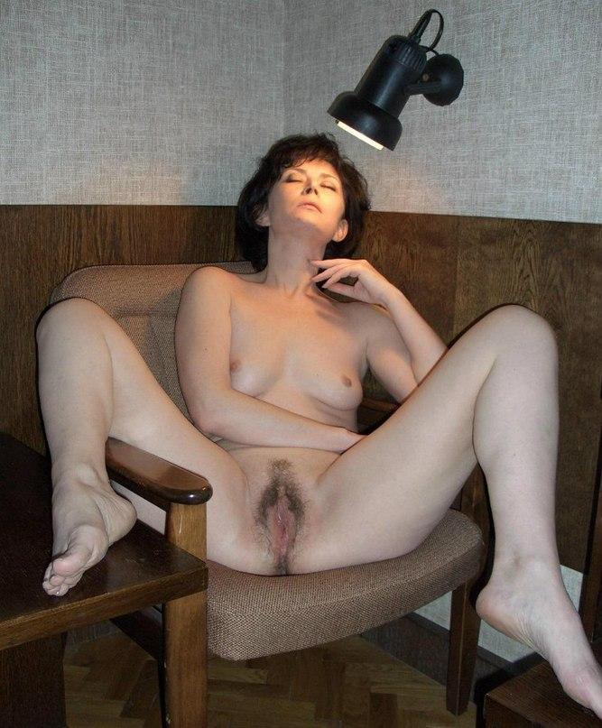 позирует на стуле под светом лампы