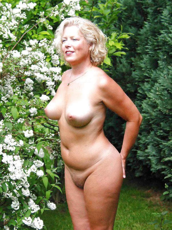 красотка в возрасте в саду среди цветов
