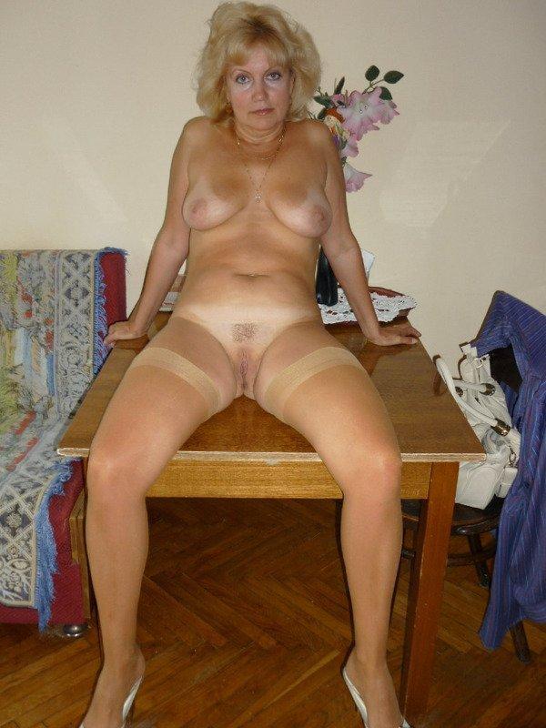 старая женщина голышом сидит на столе