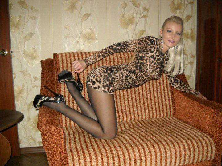 в коротком леопардовом платье на диване
