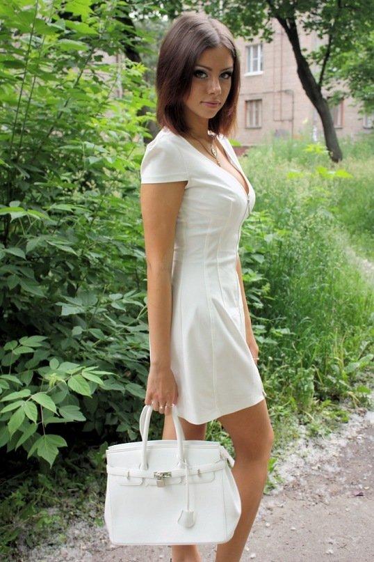 в скромном белом платьице на прогулке