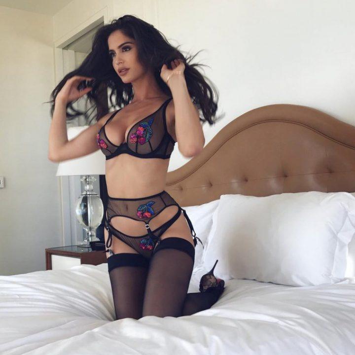 сексуальная брюнетка на кровати в нижнем белье черного цвета