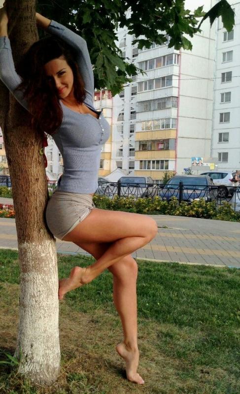 позирует у дерева, изящно изогнув спину