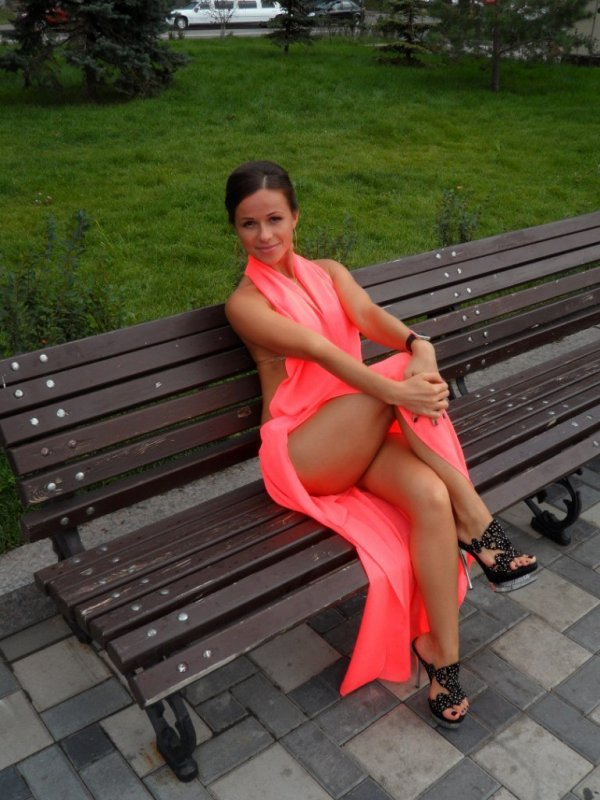 в коктейльном платье, закинув ногу за ногу