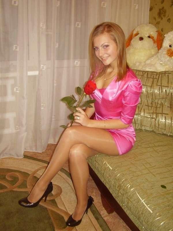 в розовом платье и с алой розой в руках
