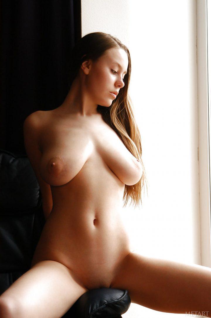 смотрит вниз, выставив грудь напоказ