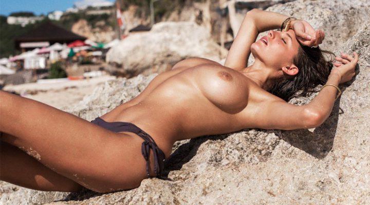 загорает топлесс на пляже под солнцем