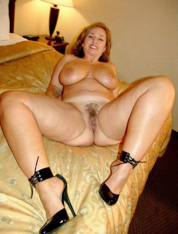 милфа в туфлях с высокими каблуками на кровати