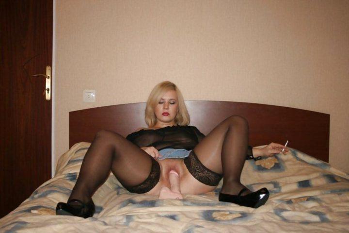 блонда в спальне на кровати удовлетворяет себя фаллоимитатором