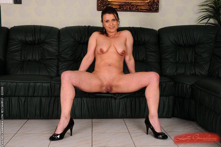 дама в 45-ти лет на диване, расставив ноги