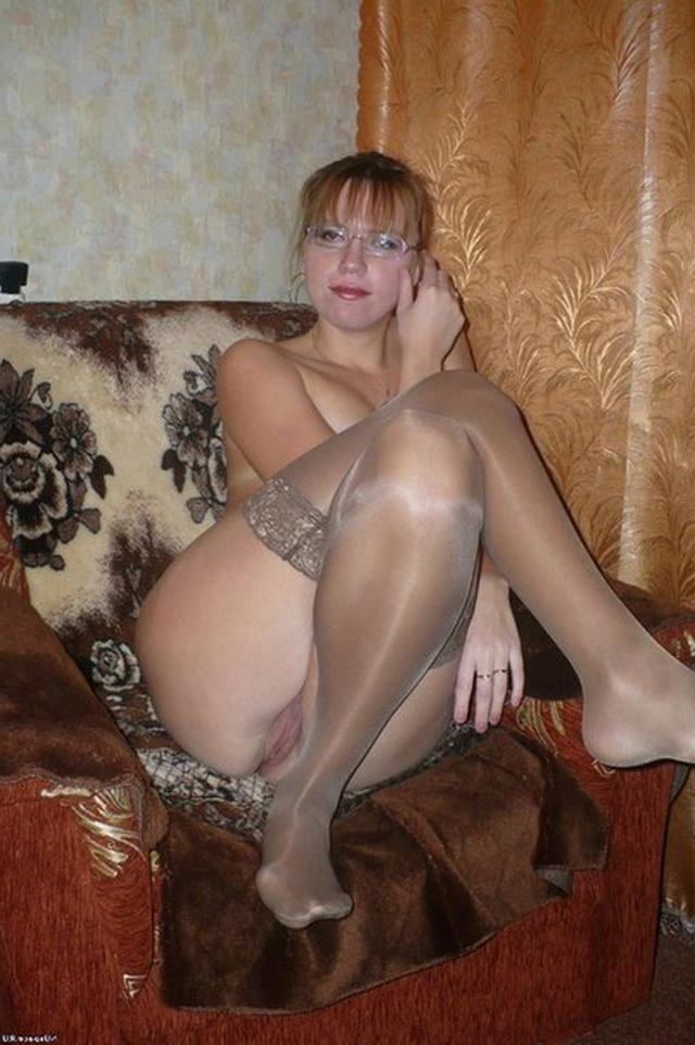 дама в возрасте позирует в нейлоновых чулках и без белья, сидя в кресле