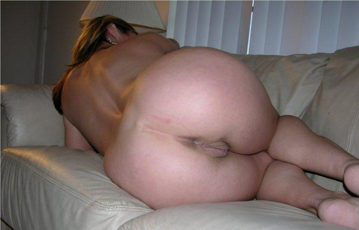 на диване без одежд сбоку