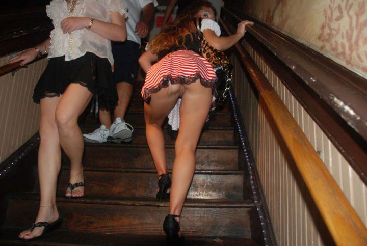 поднимается по лестнице в очень короткой юбке