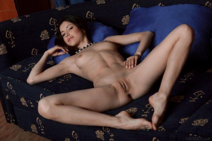 милашка с выбритой киской, засветила свои прелести между ног, лежа на диване