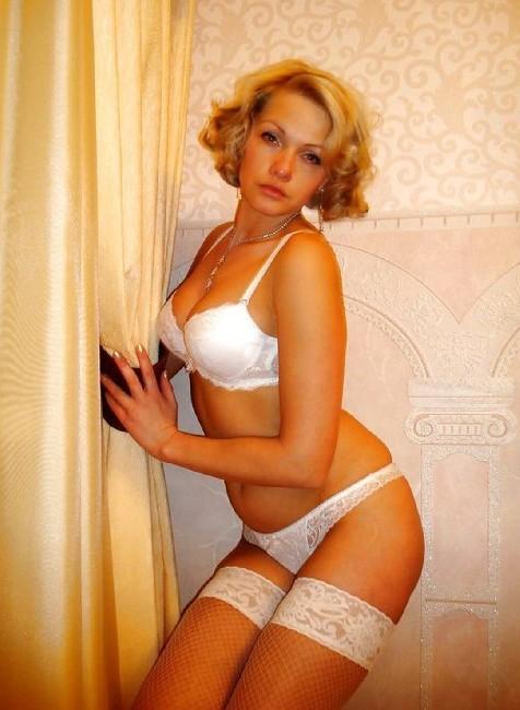 Секси женщина 40 лет в белом нижнем белье и чулках