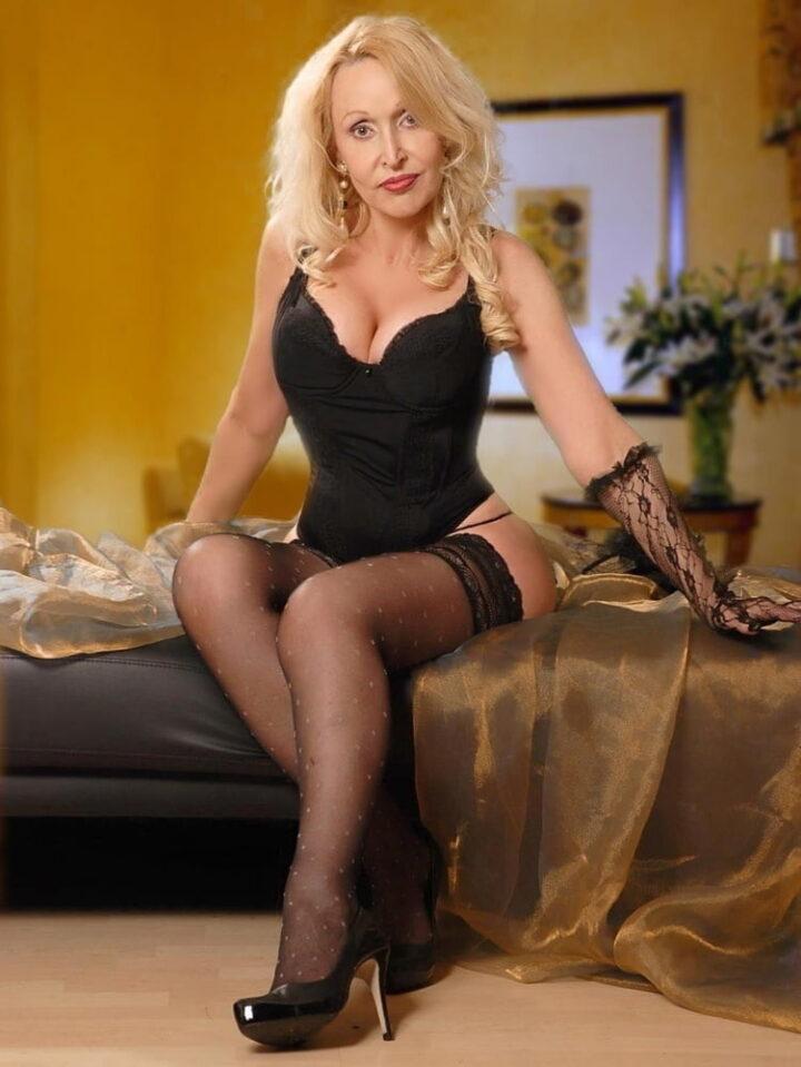 Блондиночка 40 лет в корсетном белье сидит на кровати