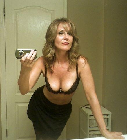 Красивая сорокалетняя женщина в лифчике смотрит в зеркало