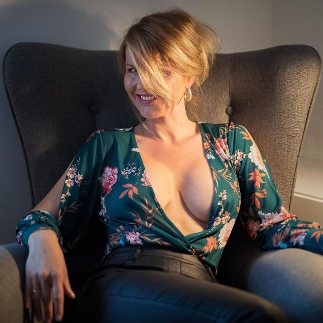 Загадочная красивая женщина 40 лет сексуально сидит в кресле
