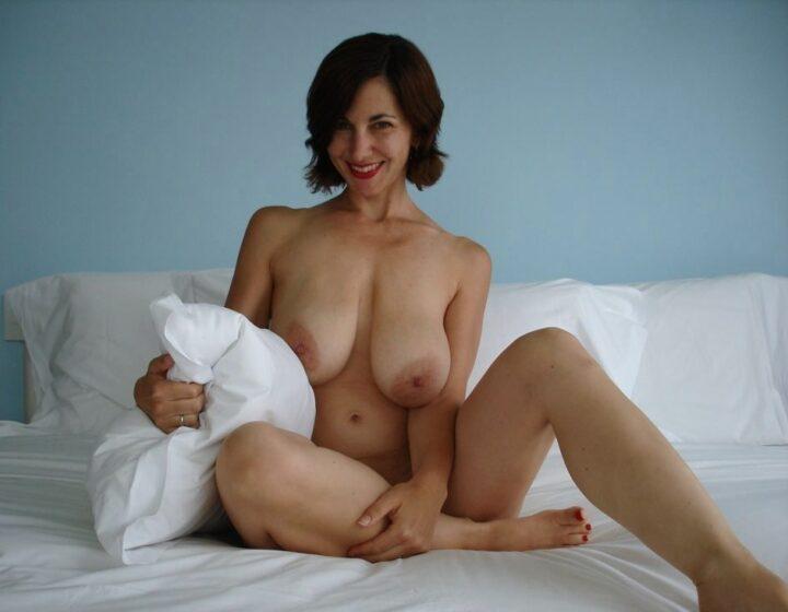 Стройная брюнектка в зрелости на кровати с голыми сиськами