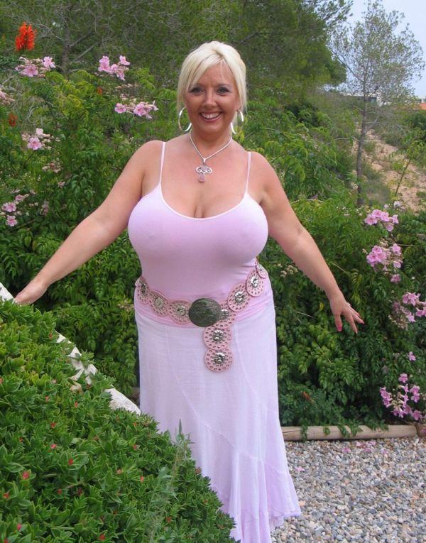 Улыбчивая зрелая блондинка в белом платье с большими дойками