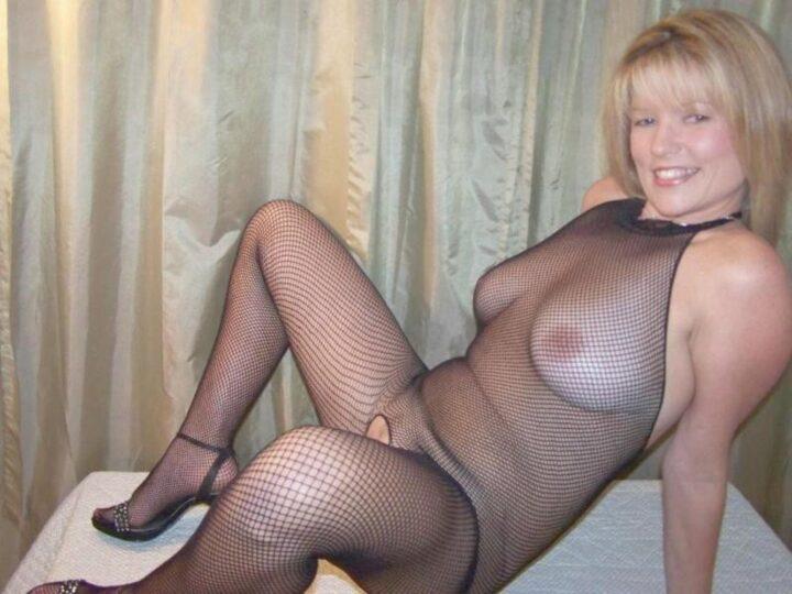Кокетливая женщина в годах сидит дома в эротической сетке на голое тело