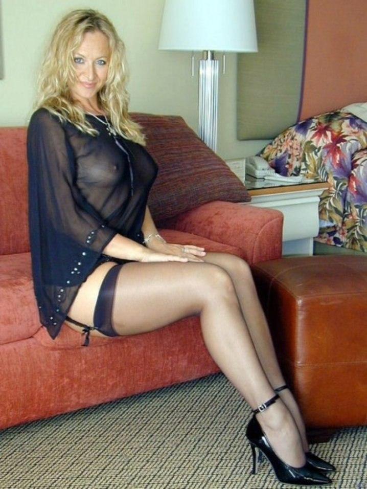 Кудрявая женщина блондинка зрелая сидит на диване в прозрачной одеже демонстрируя грудь