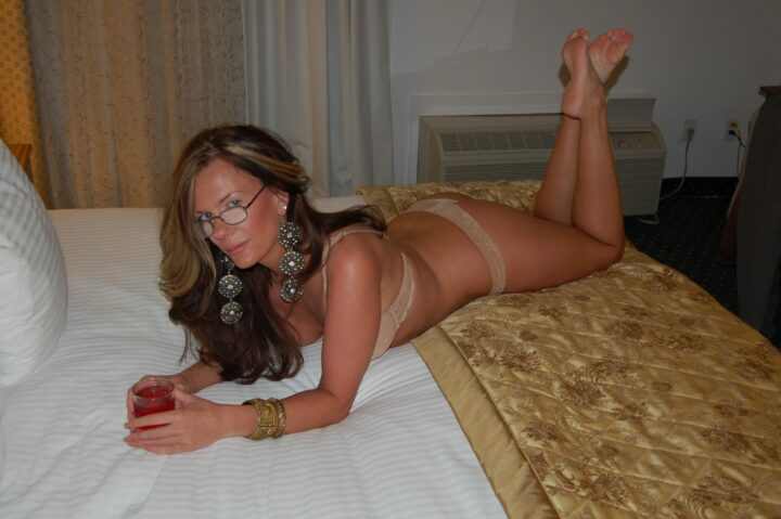 Интересная и красивая загорелая женщина лежит в бежевом белье на кровати в домашней обстановке