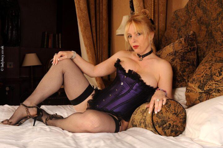 Рыжая зрелая женщина в фиолетовом корсете лежит на кровати с разведенными ногами