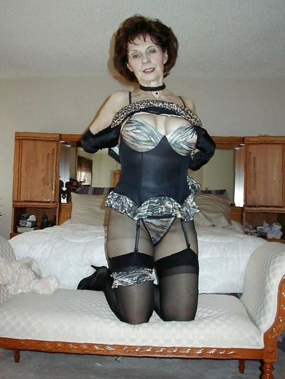 Сексуальная дама в годах стоит на коленях в чулках и белье